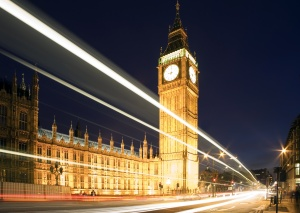 Big Ben in London at night against blue sky. London traffic