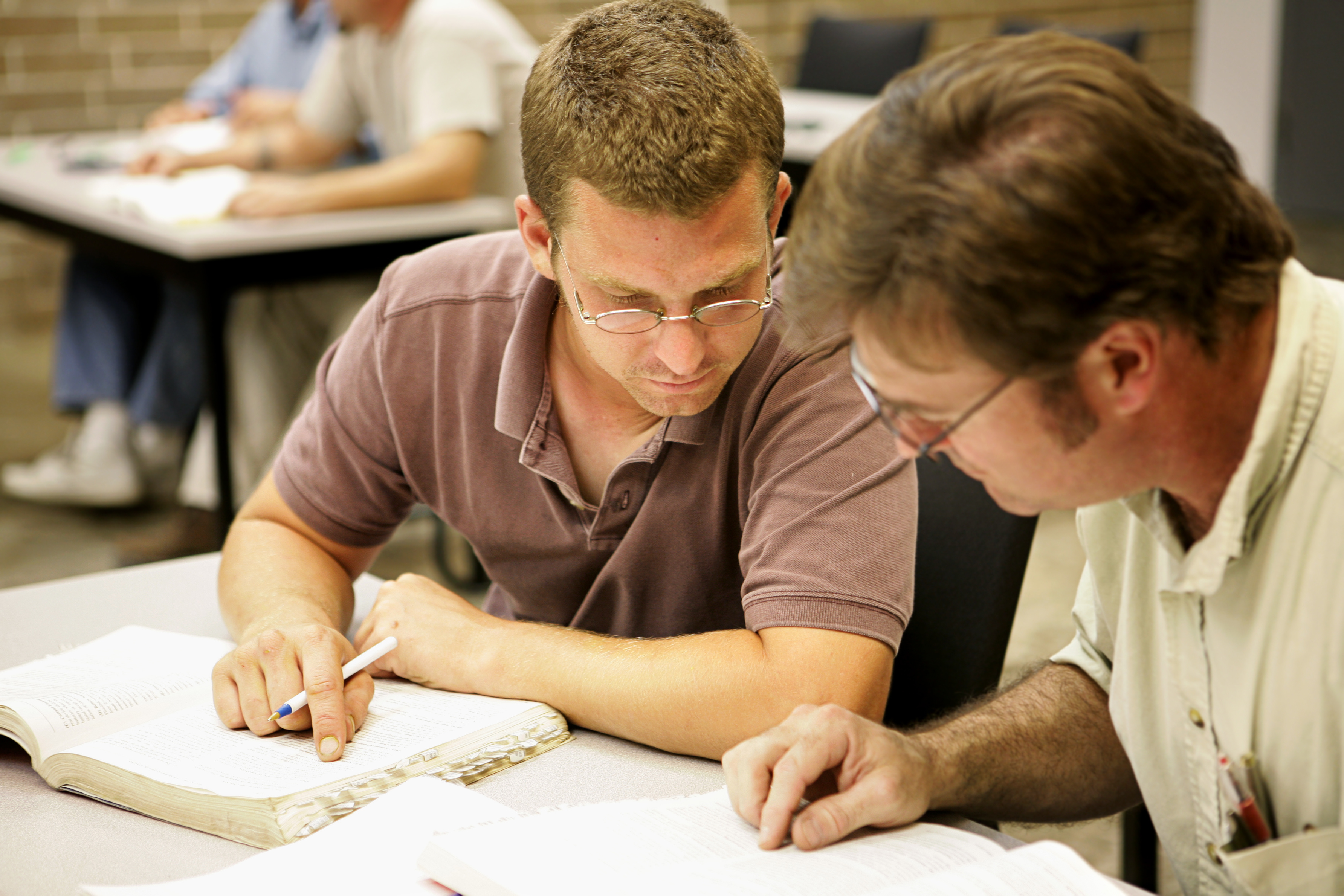 Two adult education students studying together in class.