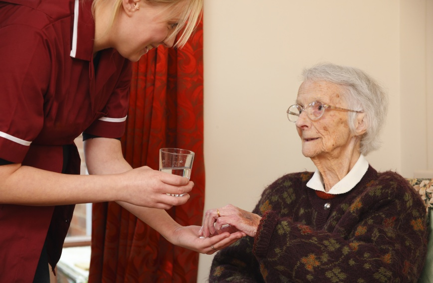 pregnant carer giving pills and medication to her elderly pacient