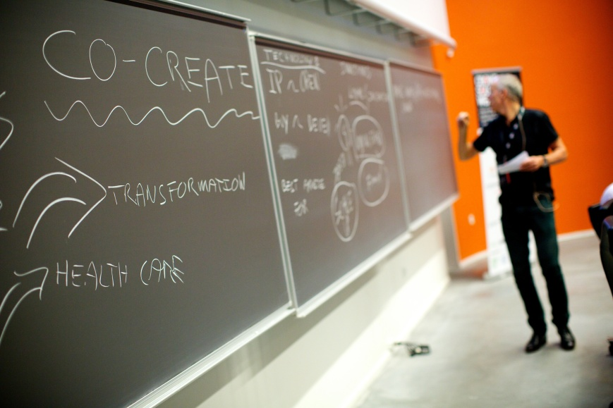 Blackboard showing the words 'Co-create', 'Transform', and 'healthcare'.