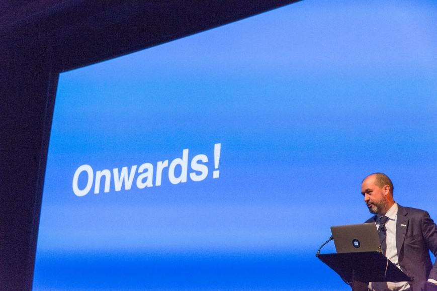 Mike Bracken, former Executive Director Digital for the UK Government, on a stage with the word 'Onwards' in the background.