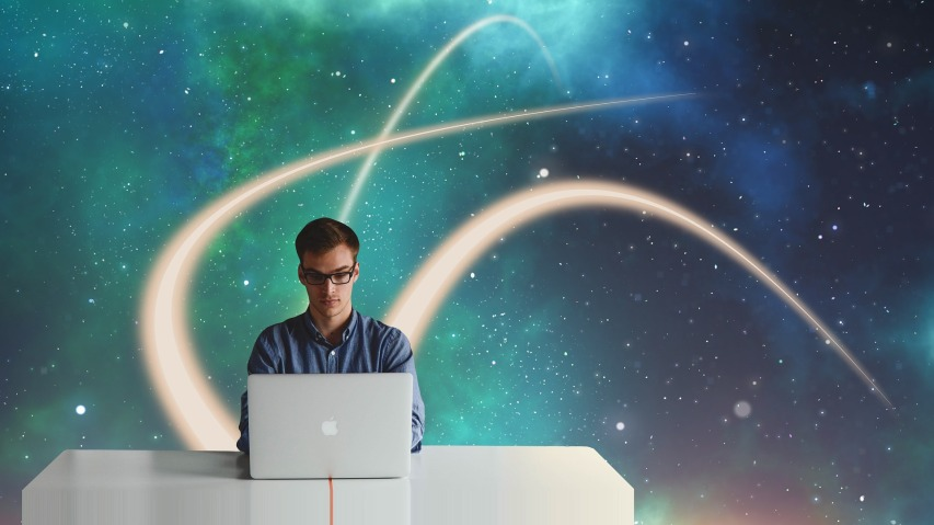 Man sitting at a desk, with stars and nebula's behind him