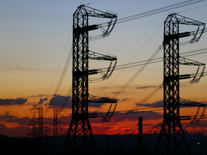 Electricity pylons with a glowing orange and red sky in the distance