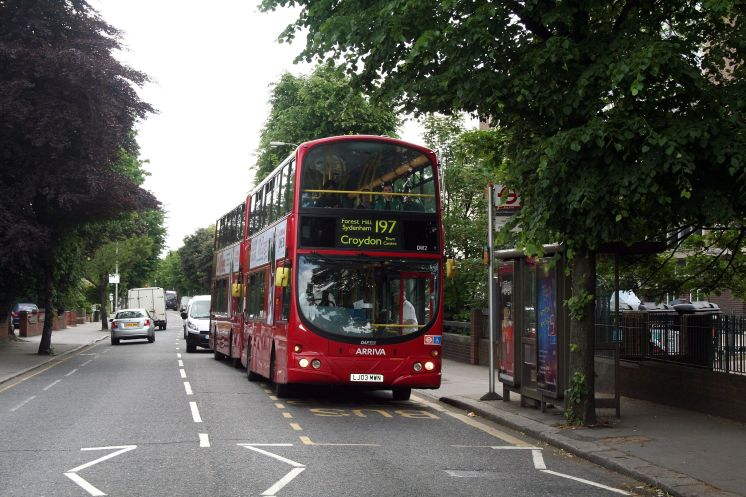 A red bus displaying its destination is Croydon