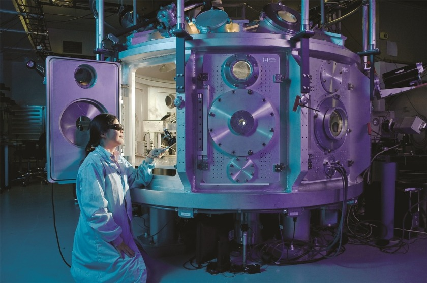 Scientist working with a large cylinder-shaped piece of lab equipment