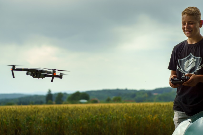 A young boy flying a drone