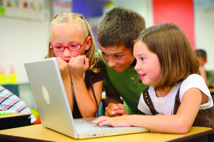 Three children leaning over a laptop
