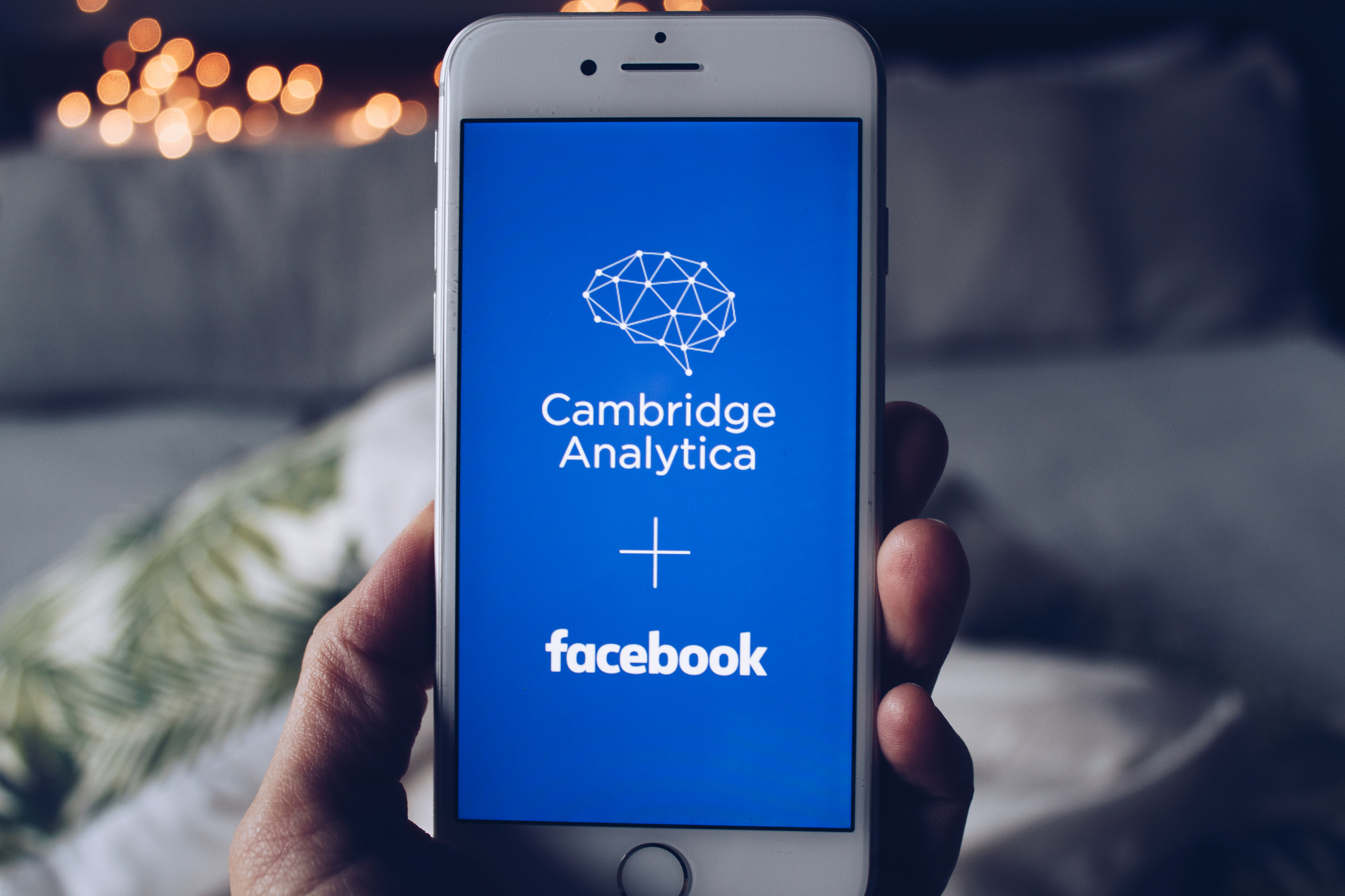 "A smart phone with the words: ""Cambridge Analytica + Facebook"""